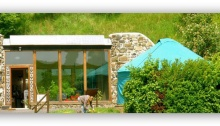 Photo of a worker in front of Earthship Fife and the yurt